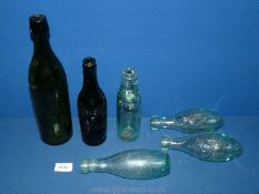 A small quantity of old pop bottles including one in dark glass.
