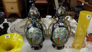 A pair of oriental lidded vases and two table lamps