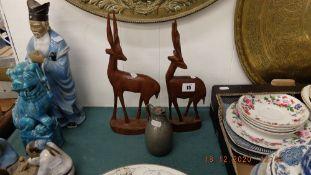 Two wooden deer figure plus a small metal jug