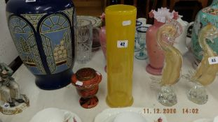 A mustard colour glass vase decorated with flowers