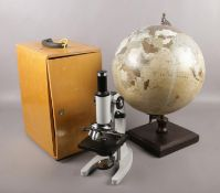 A cased Brunel microscope, along with a globe on stand.