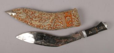 An Eastern Kukri knife in embroided and white metal mounted sheath.