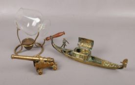 Three pieces of decorative brassware, to include gondola ink well, brandy glass warmer and a cannon.