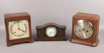 Three oak cased mantel clocks. An Elliot oak cased 8 day mantel clock, Norland and a carved