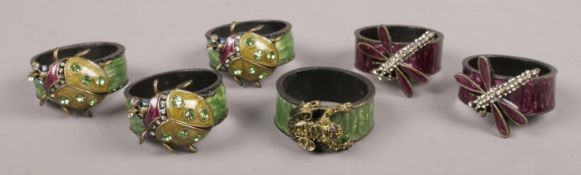 Six enamelled serviette rings, five decorated with paste set insects, the other with a frog.