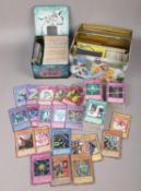 Two tins of Yu-Gi-Oh trading cards to include shiny examples etc.