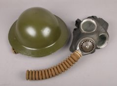 A military Brodie type helmet, along with a WWII gas mask stamped Avon 1-41 and baring the broad