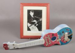A Selco Tommy Steele plastic guitar, along with a framed autographed photograph.