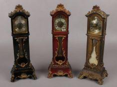 Three miniature grandfather alarm clocks. (33cm high) Hinge on black clock broken. Catch on back