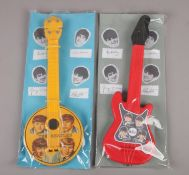 Two The Beatles plastic guitars, both in packaging, 41cm.