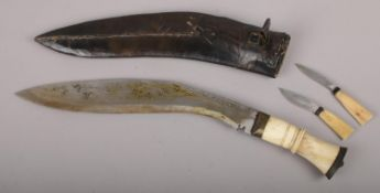 A gurkha's kukri knife in scabbard with carved bone grip and two smaller accompanying knives.