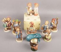 A quantity of mostly Goebel hummel figures to include boy carrying shoes, figures sat on branches,