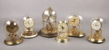 Six torsion clocks, to include Schatz, Kundo etc. all under plastic domes.
