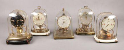 A Haller torsion clock under glass dome, along with four similar Schatz torsion clocks, all under
