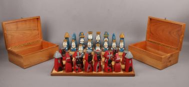 Hand carved and painted wooden chess set and board, together with two wooden storage boxes. Board