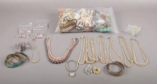 A large collection of costume jewellery to include, a selection of faux pearl necklaces, bangles,