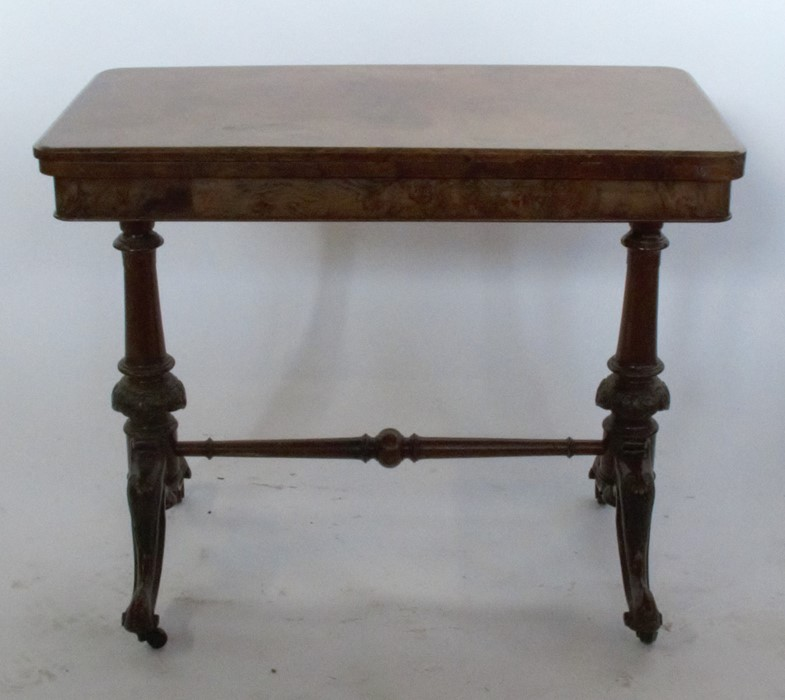 Lot 24 - A 19th century walnut fold over games table, of rectangular form, raised on carved and turned
