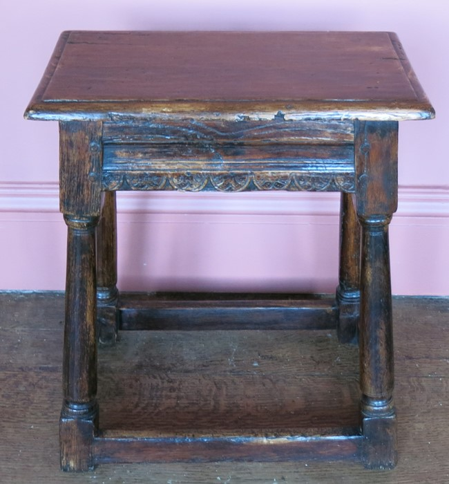 Lot 15 - A 17th century style oak joint stool, raised on four turned legs united by a stretcher, width 16ins