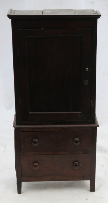 Lot 51 - A late Georgian oak cupboard, with rectangular doors opening to reveal shelves, raised on an