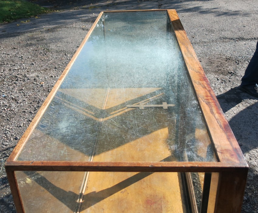 Lot 18 - An oak and glass shop play counter, with sliding doors and shelves, 70ins x 23ins x 35.5ins