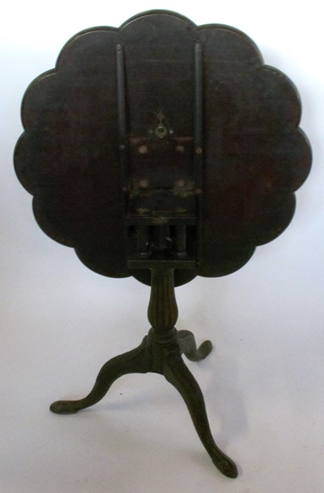 Lot 36 - A 19th century mahogany tilt top table, the circular top with lobed edge having carved decoration,