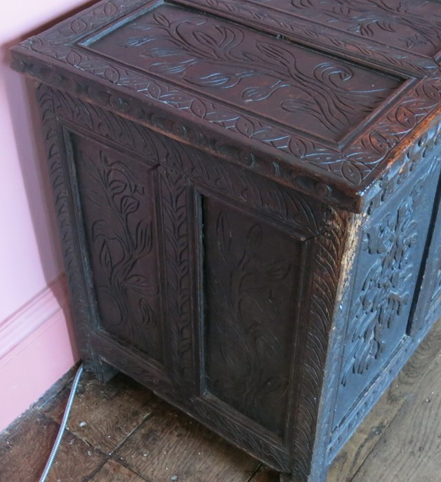 Lot 14 - An Antique oak coffer, with four carved panels to the rising lid, three carved panels to the front