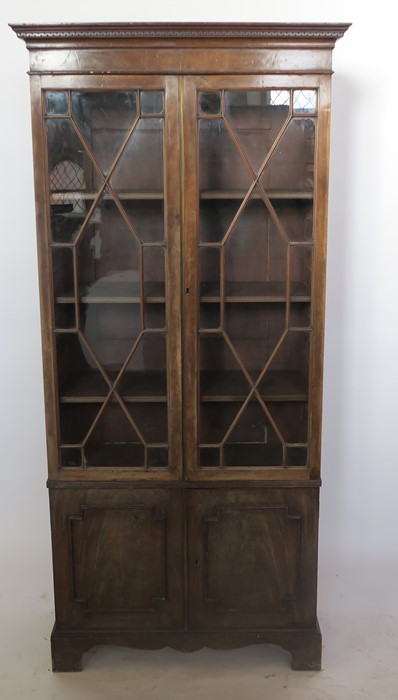 Lot 44 - A 19th century mahogany display cabinet, with a pair of astragal glazed doors, over a pair of