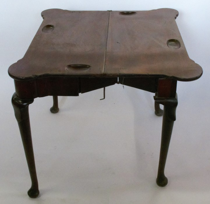 Lot 34 - A 19th century mahogany fold over games table, having a shaped rectangular top, the games surface