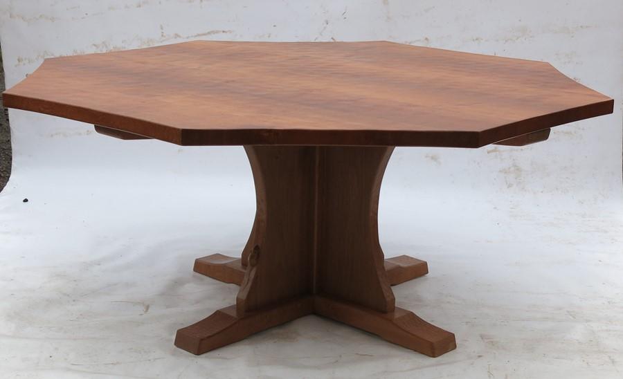 Lot 59 - Robert Thompson Mouseman, an oak octagonal dining table, raised on a cross base, with adzed