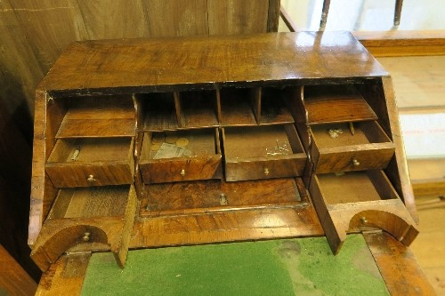 Lot 43 - An Antique walnut bureau, the sloping fall front opening to reveal drawers, pigeon holes and a well,