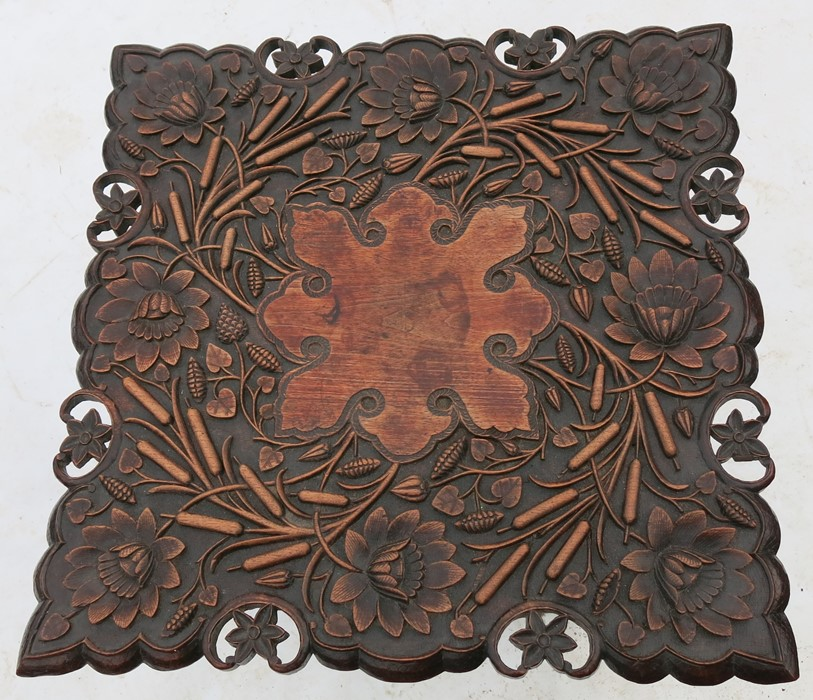 Lot 20 - An Eastern mahogany carved square table, the top heavily carved with flowers and leaves, on a carved