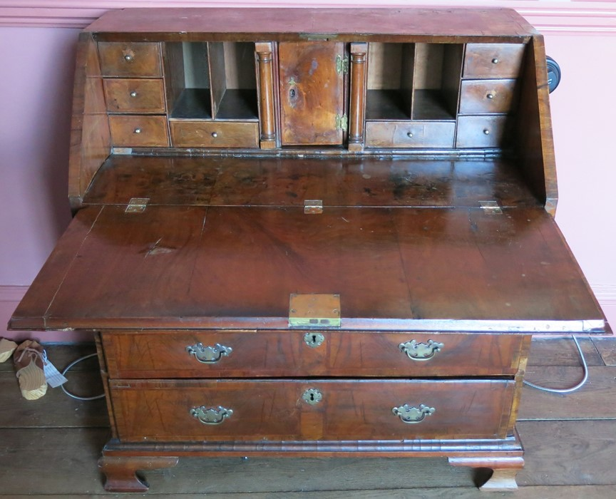 Lot 17 - An 18th century walnut bureau, fitted with a curvetto drawer below the fall flap, over two short and