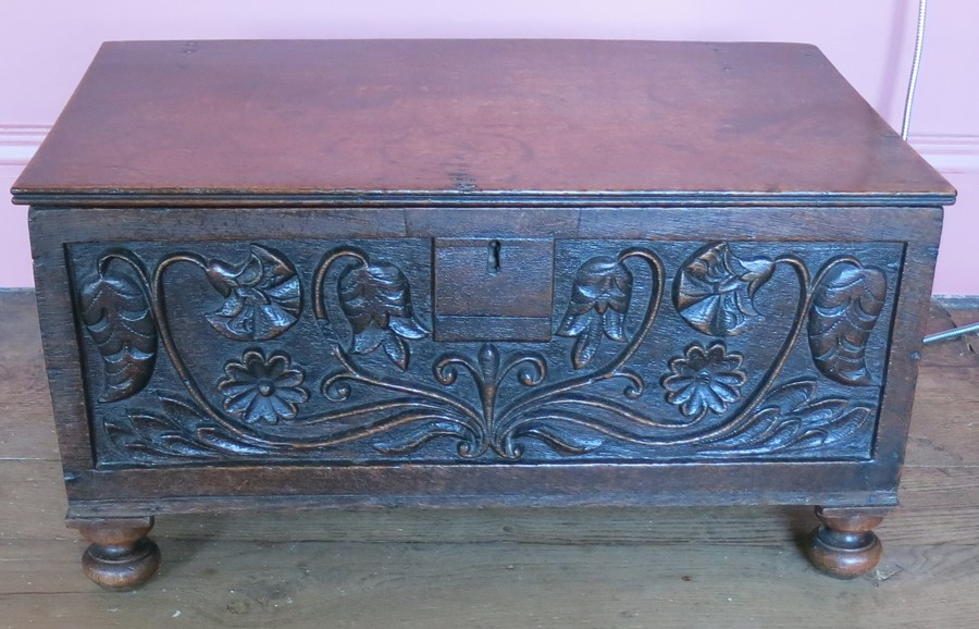 Lot 12 - An Antique oak bible box, having a plain rising lid, floral carved to the front and raised on ball