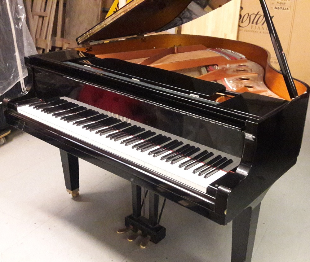 Lot 23 - Yamaha (c1977) A 4ft 11in Model GB1grand piano in a bright ebonised case on square tapered legs.