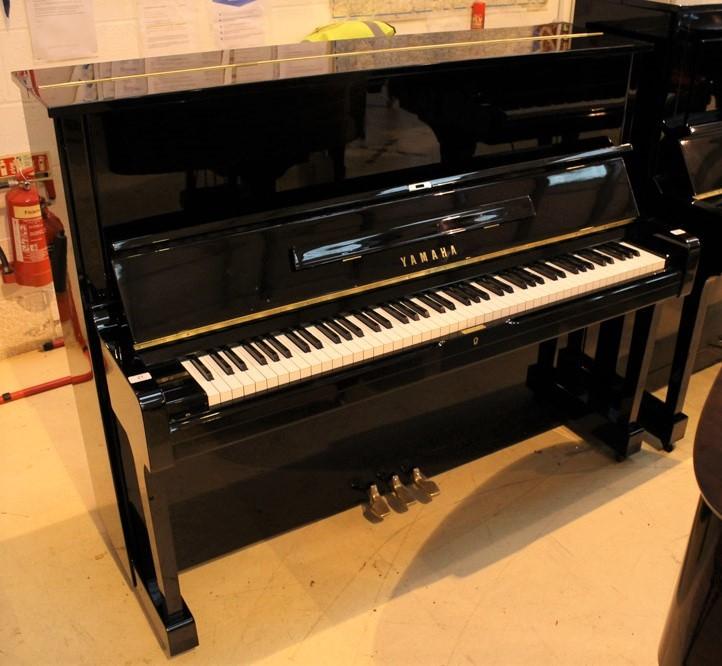 Yamaha (c1977) A Model U1H upright piano in a bright ebonised case.