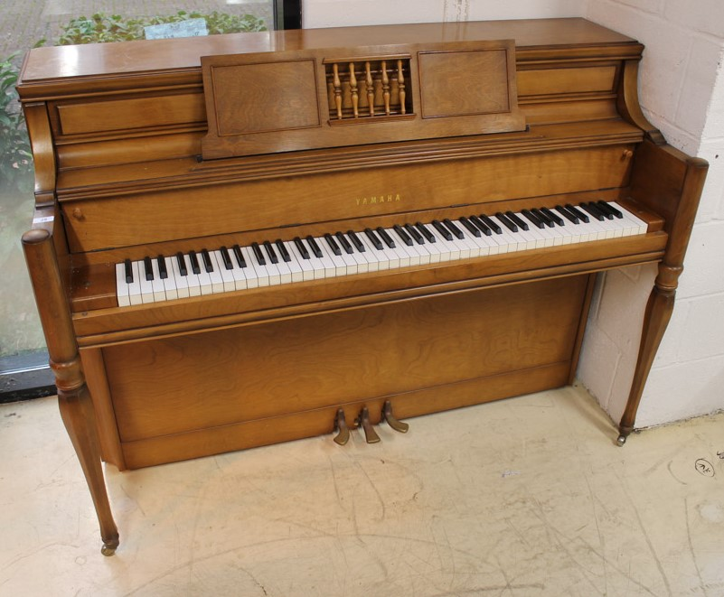 Yamaha (c1971) An upright piano in an American 'spinet' style case; together with a matching stool.