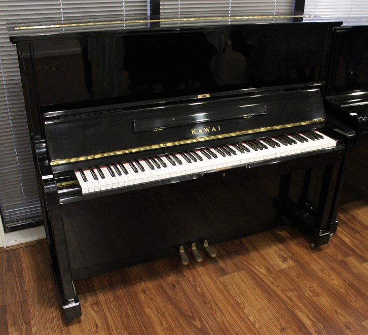 Kawai (c1985) An upright piano in a traditional bright ebonised case;
