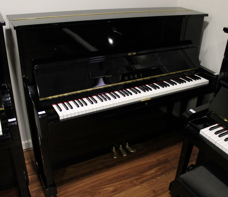Miki A 121cm Model MU1D upright piano in a bright ebonised case.
