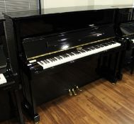 Kemble (c2014) A Model K121CL upright piano in a bright ebonised case.