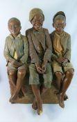A large Goldscheider pottery model of three boys sitting on a brick wall by B Haniroff,