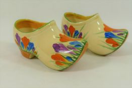 A pair of Clarice Cliff crocus pattern clogs, with painted Bizarre pattern marks,