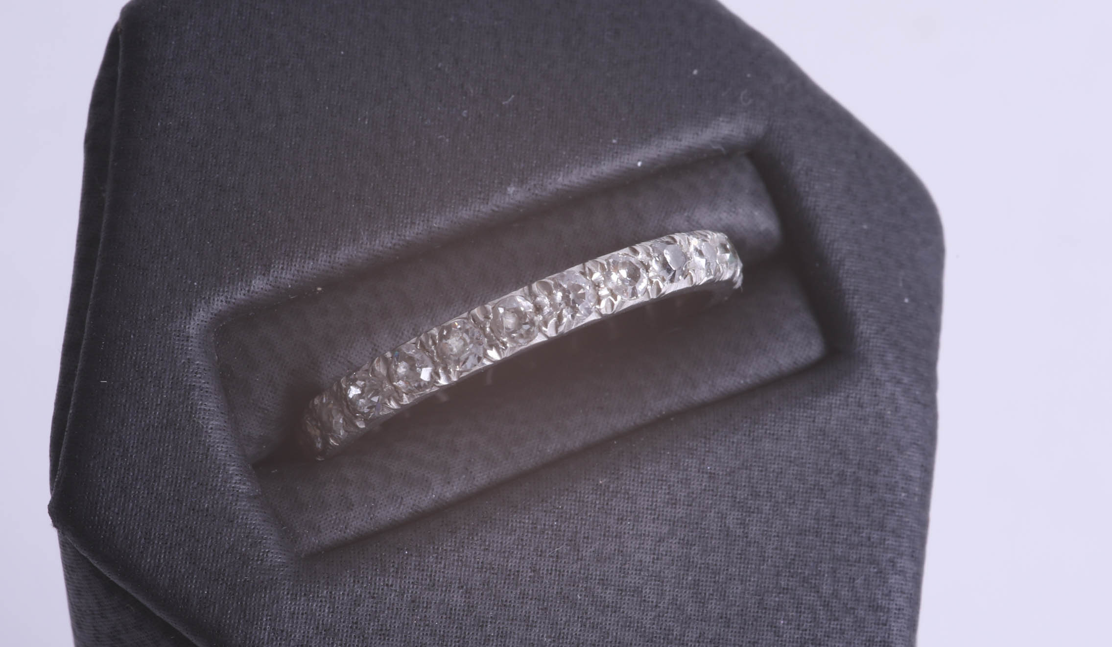 Lot 063 - A full band eternity ring set in white metal (lacks two stones), size Q.