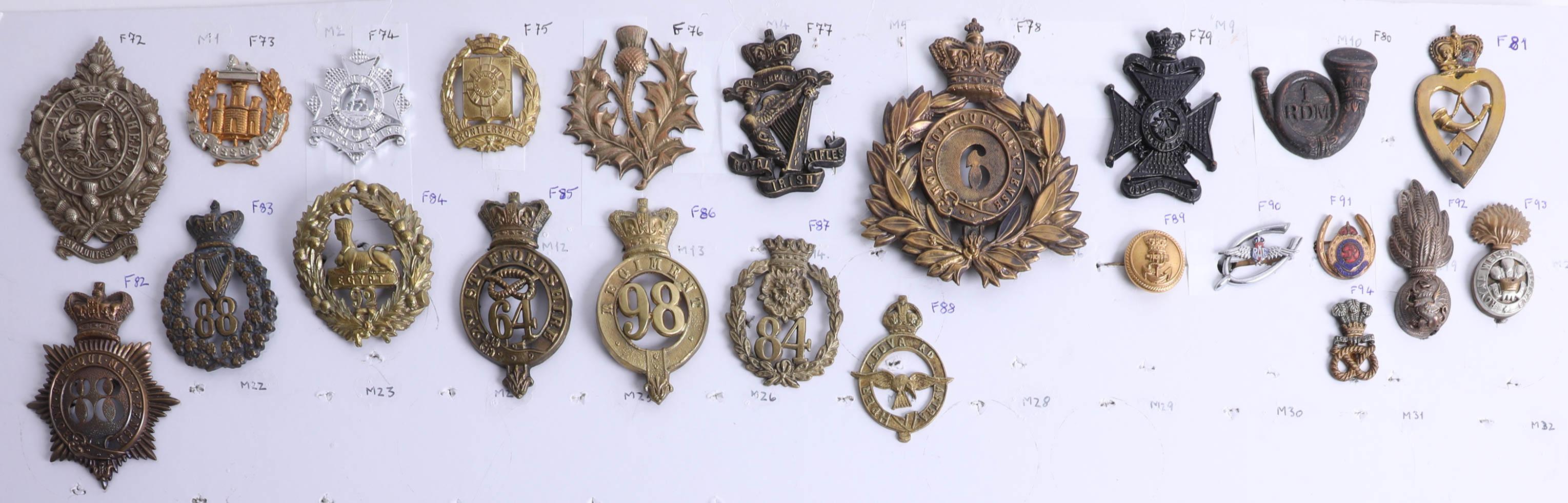 Lot 006 - A collection of approx. 94 military cap badges displayed on two sheets, including an 1860 shako star