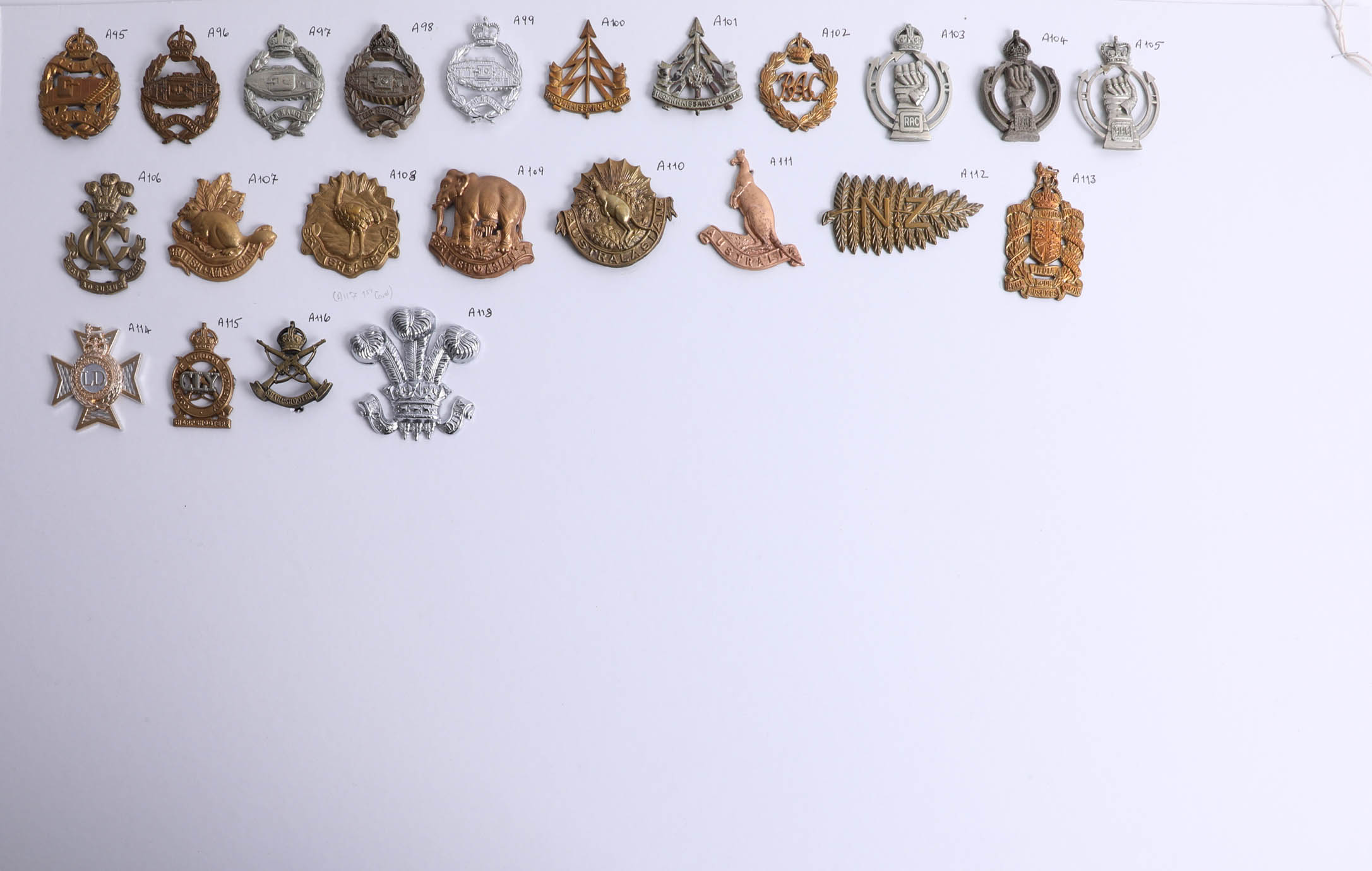 Lot 001 - A collection of approx. 119 military cap badges displayed on two sheets, including a helmet plate
