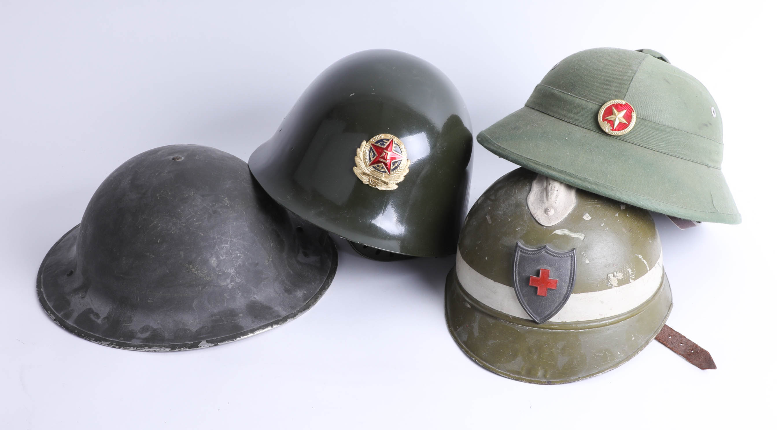 Lot 018 - Four helmets including Chinese Jin Dong, Chinese pith helmet and English WWII helmet. Part of the