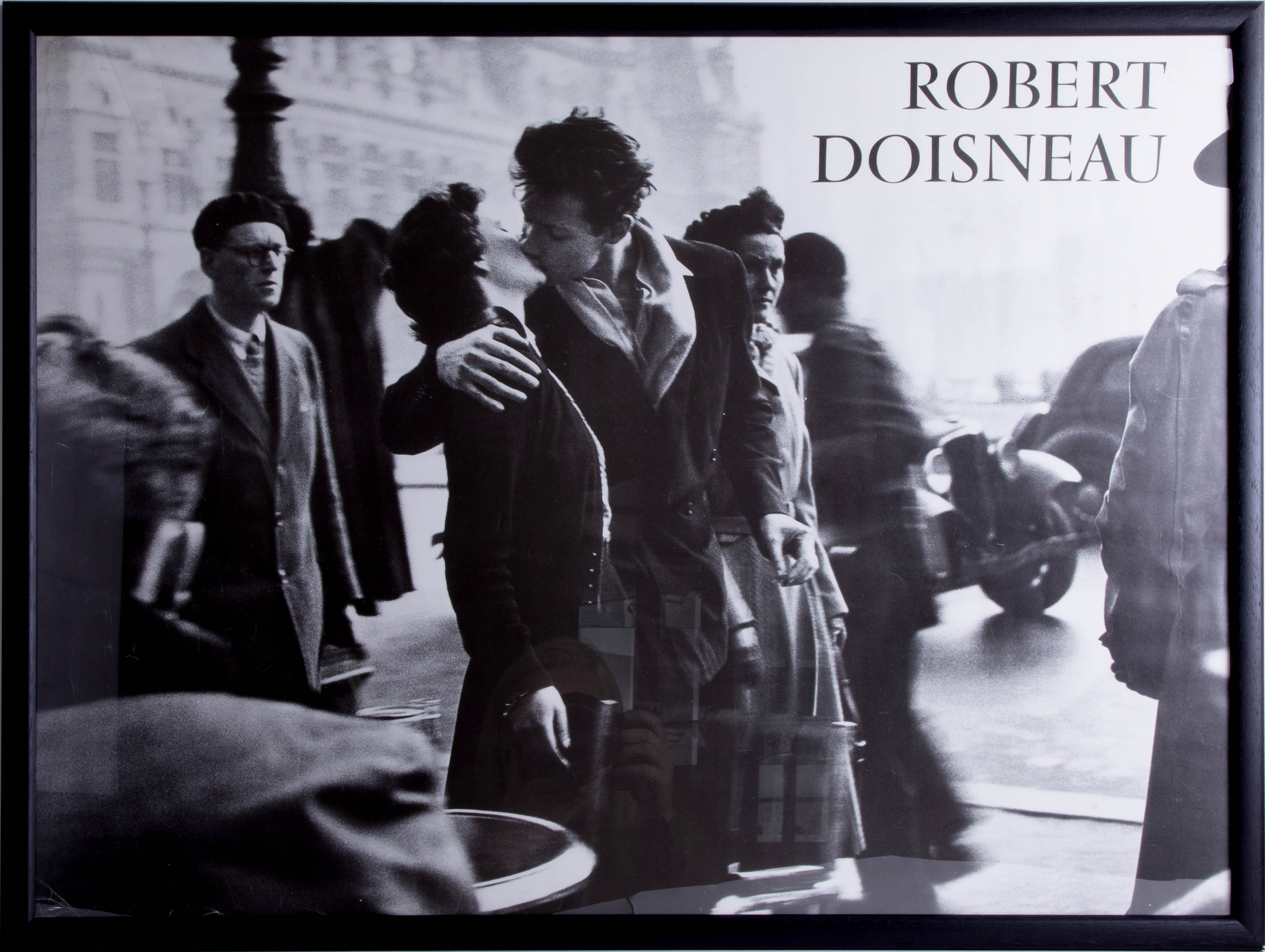 Lot 038 - Robert Doisneau, 'The Kiss by the Town Hall, Paris 1950' photographic poster, framed and glazed,