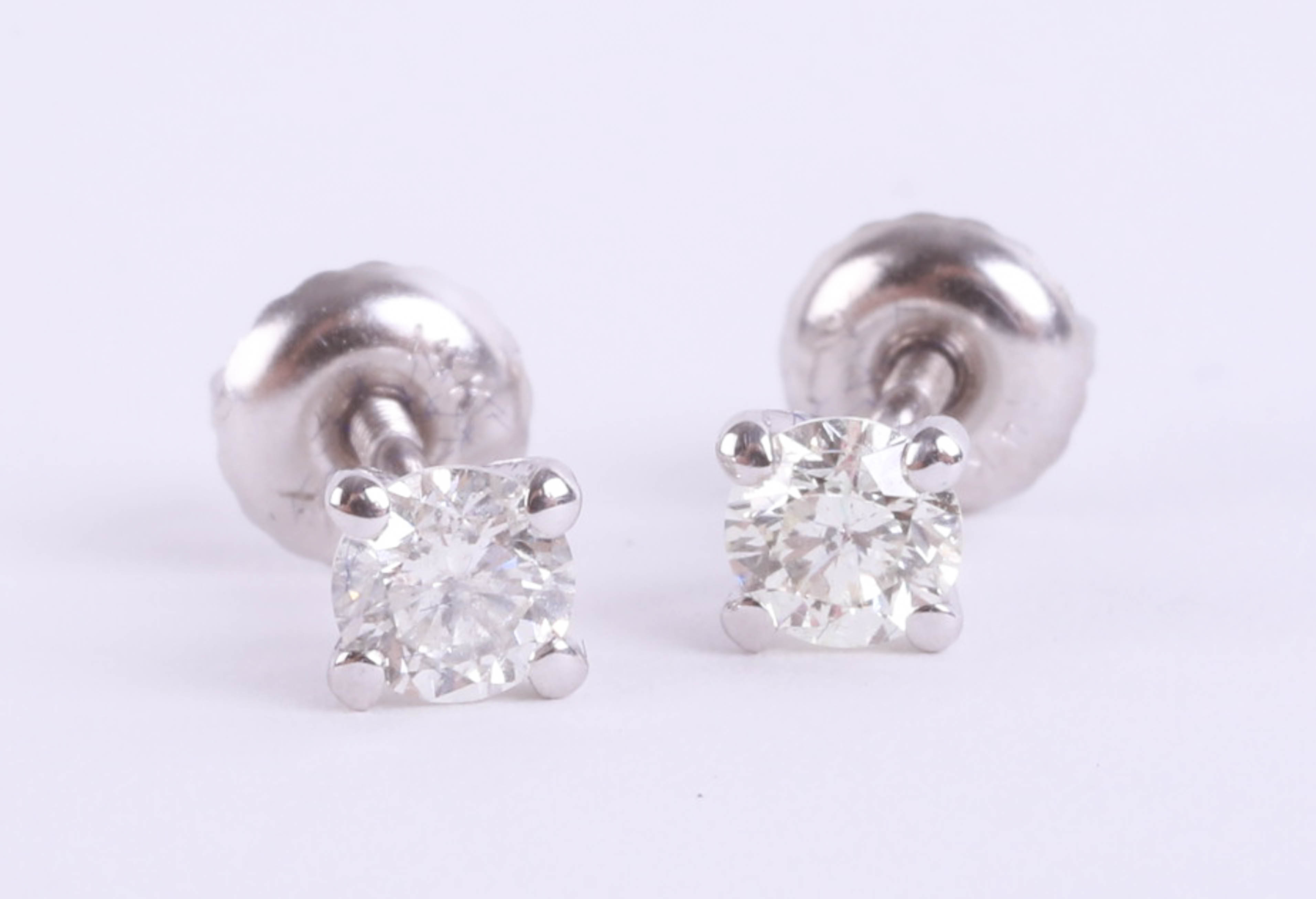 Lot 034 - A pair of 14k white gold round cut diamond stud earrings, colour D-E, clarity VS1, total carat