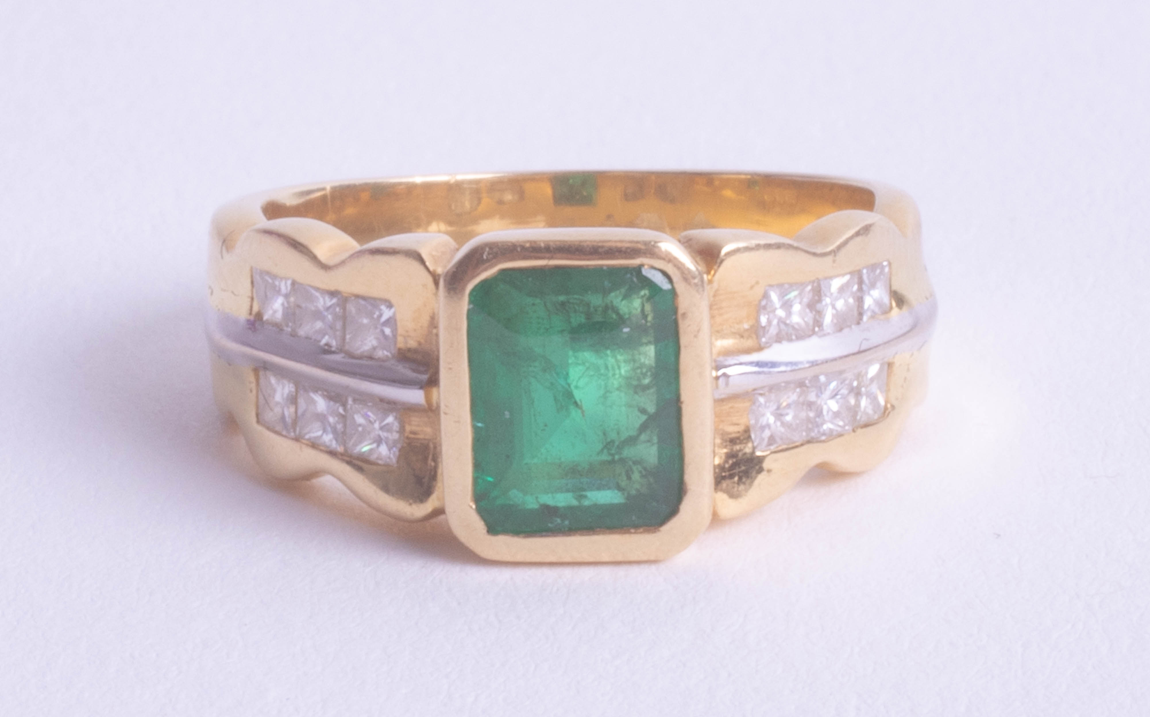 Lot 030 - An 18ct yellow gold emerald and diamond ring, size O.