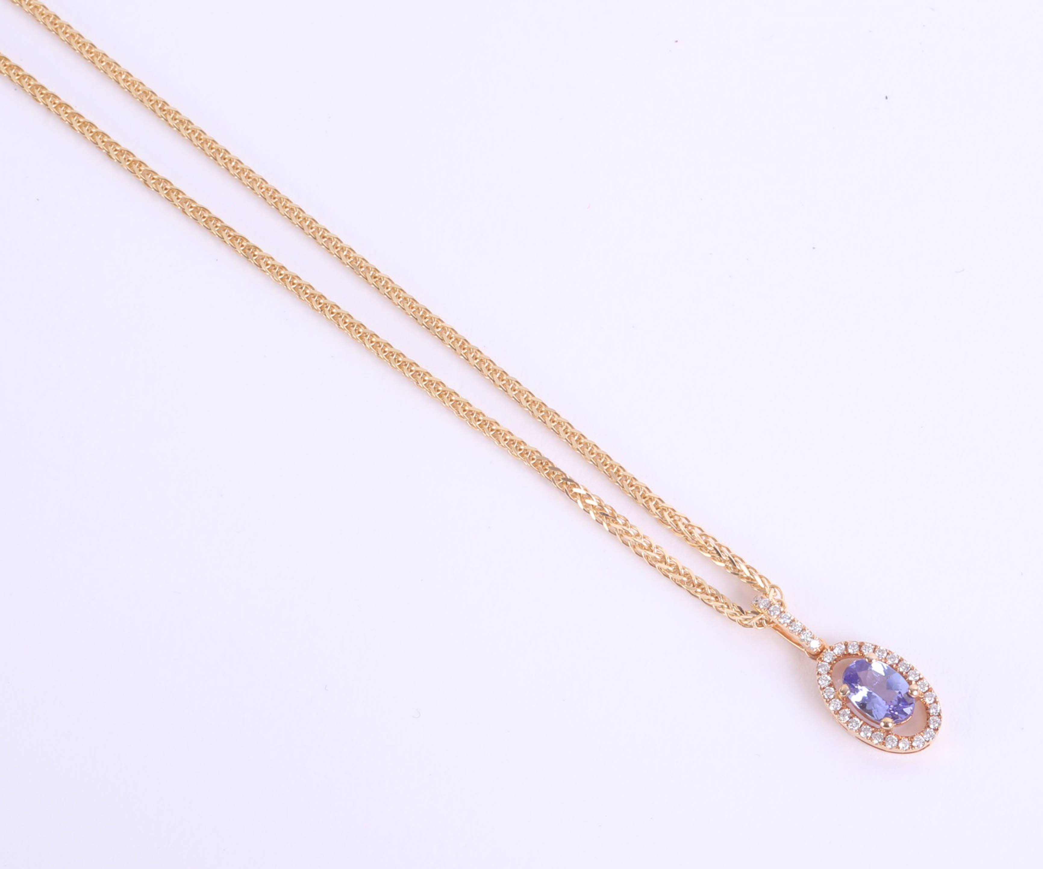 Lot 040 - An 18ct tanzanite and diamond cluster pendant set in yellow gold on fine 18ct chain, total weight