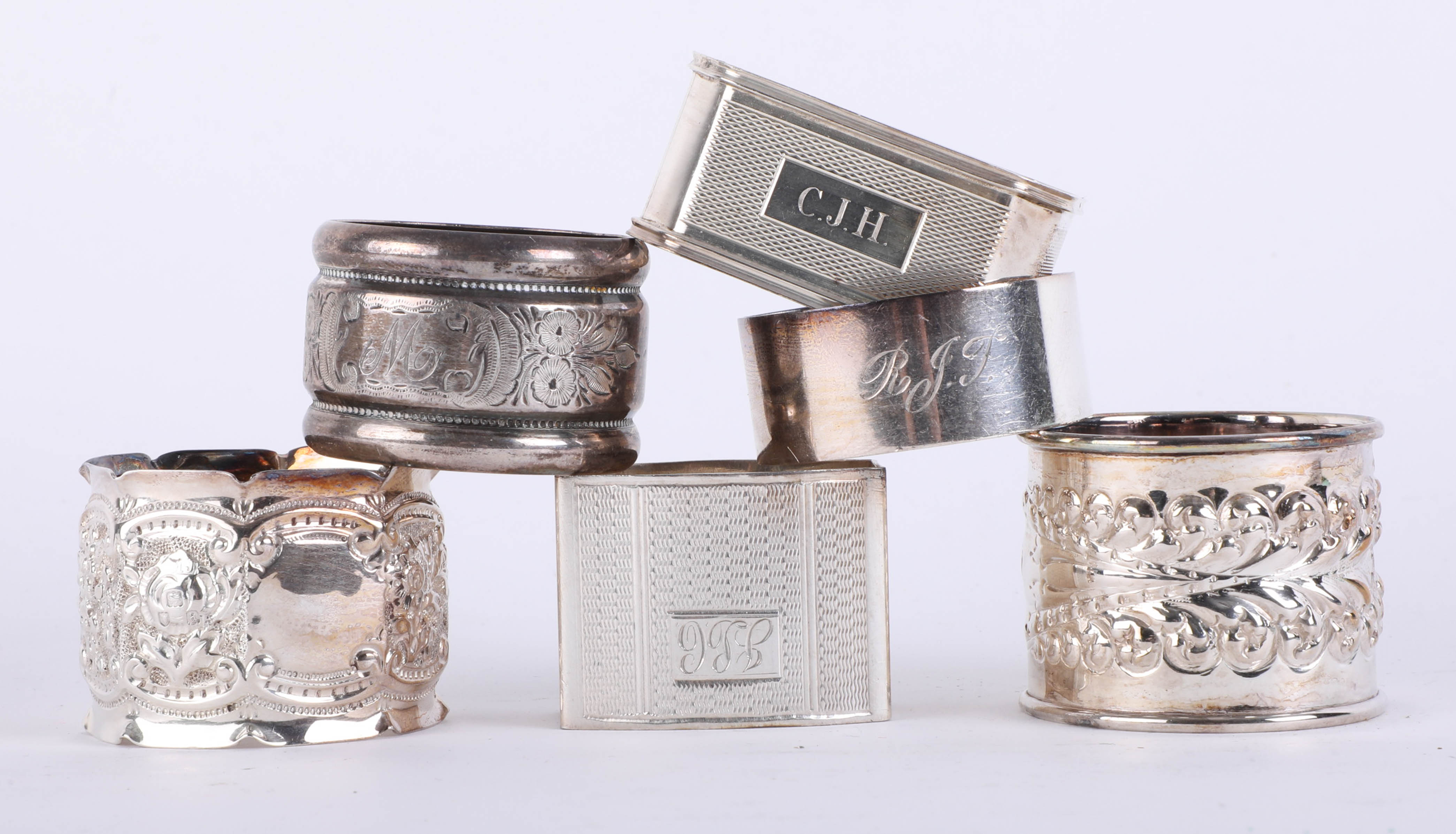 Lot 012 - Harlequin set 6 silver hallmarked fancy napkin rings with embossed and engine turned decoration,